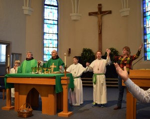 Father Neri Greskoviak, OFM, assistant at St. Mary, Father Jeff Scheeler, OFM, provincial minister, and other liturgical ministers pray the Our Father during Mass on Jan. 24. (The Catholic Post/Tom Dermody)
