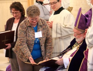 Anna Catour presents the Book of the Elect from Christ the King Parish in Moline to Bishop Jenky. The book contains the names of those who will be baptized at Christ the King at the Easter Vigil. (The Catholic Post/Jennifer Willems)