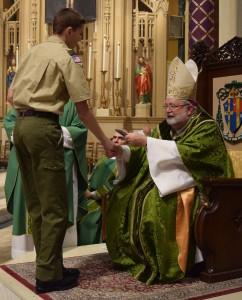 Luke Albertson of Troop 57 (St. Luke, Eureka) receives the Pope Piux XII medal from Bishop Jenky. (The Catholic Post/Tom Dermody)
