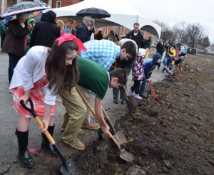 Following the indoor ceremonies, many families stepped out into the rain to play their own role in the historic day. Among those shoveling dirt at the building side for the new parish center were Elizabeth, Mark, and Matt Hanley. (The Catholic Post/Tom Dermody)