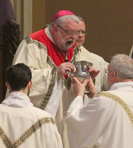 Bishop Jenky breathes over the opening of the vessel containing the sacred chrism as a sign of infusing it with the Holy Spirit. (The Catholic Post/Jennifer Willems)