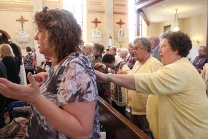 Kathy Rogiers of St. Patrick in Colona places her hand on Tammy Beeson's shoulder while praying the Our Father at the Mass that preceded the DCCW Volunteer Appreciation Lunch on April 14. (The Catholic Post/Jennifer Willems)