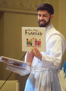 The students of Holy Cross School gave Deacon Pica several books to use in his priestly ministry. (The Catholic Post/Tom Dermody)