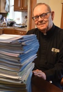 Msgr. Swaner poses with a stack of bulletins from his 13 years as pastor of St. Mary Parish in Utica. He has written a weekly bulletin column for the past 34 years. (The Catholic Post/Tom Dermody)