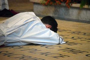 Priesthood candidate Deacon Michael Pica prostrates himself on the cathedral sanctuary floor while the assembly chants the Litany of the Saints. (The Catholic Post/Tom Dermody)