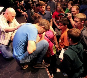 "Chris Stefanick prays with a group of students following ""Reboot Live"" on Spril 27 in Washington. (The Catholic Post/Jennifer Willems)"