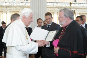 "Bishop Jenky greets Pope Benedict XVI as he presents the ""positio"" on the life of Archbishop Fulton J. Sheen in 2011. The ""positio"" is the official position paper on why the Catholic Church should recognize Archbishop Sheen as a saint. (CNS file photo/L'Osservatore Romano)"