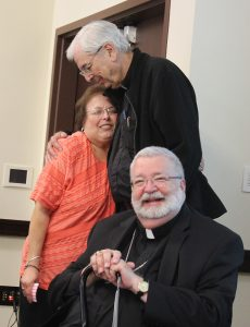 As Bishop Jenky looks on, Barb Shrode, who is retiring as principal of St. Paul School in Macomb, shares a hug with Msgr. Richard Pricco, pastor. They have worked together for 19 years. (The Catholic Post/Jennifer Willems)
