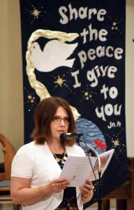 In front of a banner proclaiming a scriptural message of peace, Stephenie Adams reads a reflection assuring the Holy Spirit is with us. (The Catholic Post/Tom Dermody)