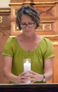 Amy Mack pauses with a candle during the Prayer Service for Peace and Healing in our Country. She led a prayer to strengthen and bless those who are comforters. (The Catholic Post/Tom Dermody)