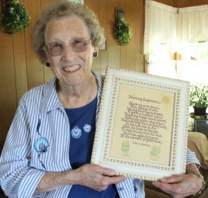 "Mary Wiesbrock holds a framed copy of her poem ""Morning Inspiration."""