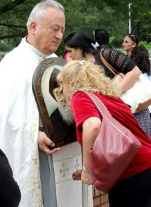 A woman venerates the image of St. Sharbel, held by Chorbishop Elia. (The Catholic Post/Jennifer Willems)