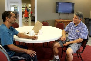 Deacon candidate Ed Mallow spends time in conversation with Andy McAdory in the new Spiritual Center at Sophia's Kitchen in Peoria. (The Catholic Post/Jennifer Willems)