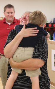 Three-year-old Kevin Markiewicz gets some loving support from his mother, Melissa Anfield, as she prepares to leave him with the teachers at the new preschool building at Holy Cross in Champaign on Aug. 17. Waiting to offer a hug on the first day of school is Kevin's father, Tony Markiewicz. (The Catholic Post/Jennifer Willems)