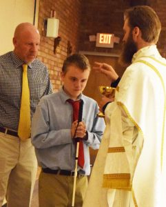 Anthony Stone -- accompanied by Randy Simmons, principal of Peoria Notre Dame --- receives a blessing from Father Adam Stimpson, school chaplain, during Mass on Sept. 12, his first day as a Notre Dame student. (The Catholic Post/Tom Dermody)