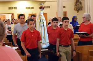 Costa Catholic Academy students James Kisler, Michael Younes and Jamie Olson help carry the statue into Corpus Christi Church in Galesburg on Sept. 16. (The Catholic Post/Tom Dermody)