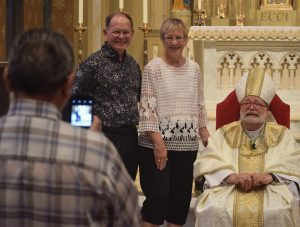 Fernando Rios takes a photo of friends Don and Marty Huber as they pose with Bishop Jenky after the Anniverary Mass. Both the Hubers and Rios are members of Christ the King Parish, Moline, and celebrated their golden wedding anniversaries in 2016. (The Catholic Post/Tom Dermody)
