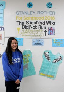 "Eighth-grader Sophia Sison of St. Joseph School in Pekin stands next to the ""campaign"" display her team created for Father Stanley Rother. (The Catholic Post/Jennifer Willems)"