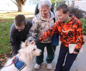Bailey welcomes gentle strokes and joyful greetings from Alexander Jackson, Joan Jackson and Mark Jackson before Mass at Sacred Heart Church in Rock Island. Therapy dogs like Bailey are trained to give loving comfort and accept the attention of those they encounter. (The Catholic Post/Jennifer Willems)