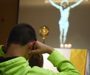 Ben Lange of Blessed Sacrament Parish in Morton prays during a candlelit Holy Hour of Eucharistic adoration. (The Catholic Post/Tom Dermody)