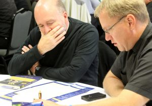"""Father Bill Miller, IC, left, and Father Chris Haake look over the pull-out chart that is part of """"Hundredfold: A Guide to Parish Vocation Ministry."""" (The Catholic Post/Jennifer Willems)"""