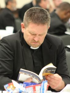 Father Kevin Creegan, pastor of parishes in Tiskilwa and DePue, leafs through a guide to parish vocation ministry written by speaker Rhonda Gruenewald. (The Catholic Post/Jennifer Willems)