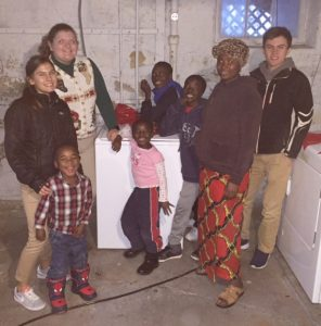 Alleman students Anna Darrow, Samantha Sharp and Augie Darrow celebrate the arrival of a washer and dryer the students bought with Maombi Kabunze and her children. (Provided photo)