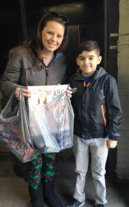 Alejandro Pompa of Visitation Catholic School, Kewanee, delivers his Angel Tree donation for the Salvation Army to Amber Troxell.  She organizes the toy drive each year in memory of her brother, Sgt. Schuyler Patch, who was killed in Afghanistan in 2009. (Provided photo)