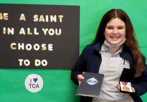 Hanna Waszkowiak holds the journal and medal the Trinity Catholic Academy student received as a fifth grader for winning the state title in the 2021 Zaner-Bloser National Handwriting Contest. (Provided photo)