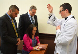 Newly ordained Father Nicolas Wilson offers a blessing to his parents, Richard and Lori Wilson, and brother Ben during a reception at the Spalding Pastoral Center that followed the ordination Mass on May 29. (The Catholic Post/Tom Dermody)