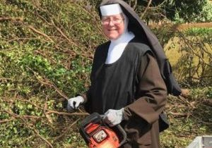 Carmelite Sister Margaret Ann Laechelin, principal of Archbishop Coleman F. Carroll High School in Miami, holds the chainsaw she used to help clean up debris following Hurricane Irma. (CNS photo/courtesy Sister Margaret Ann)