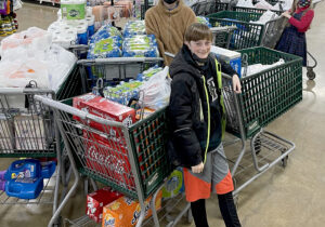 Mendota fourth-grader Cal Doyle poses with just some of the supplies he was able to buy with money donated by a local car dealership as part of the Lenten almsgiving challenge to help the homeless he proposed at Holy Cross School. (Provided photo)