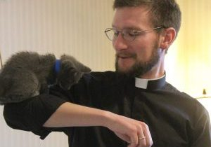 "Father Alex Millar, parochial vicar for the parishes in the Heart of Peoria Catholic Community, happily serves as a perch for his young visitor July 19. ""We had three cats when I was growing up,"" he explained. Recognizing a kindred spirit, the kittens all found their way into his office at one point or another. (The Catholic Post/Jennifer Willems)"