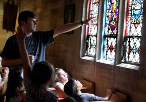 In this 2018 file photo, Brinley Kluepping gazes up as Tom Anderson, a team member for Totus Tuus, explains the various aspects of Jesus' life and ministry depicted in the stained glass windows at St. Louis in Princeton during a church tour. (The Catholic Post/Jennifer Willems)