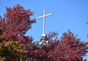 The cross above St. Patrick Church in Washington is surrounded by color in this photo from last fall. Coadjutor Bishop Louis Tylka will remember the Washington faith community on July 4 as part of his monthly prayer calendar. (The Catholic Post/Tom Dermody)